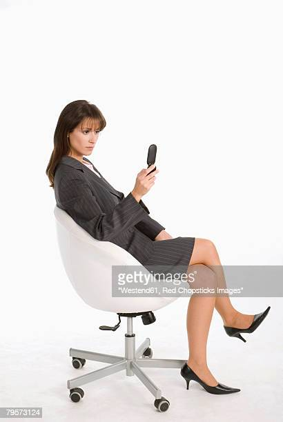 'Businesswoman sitting in chair, using mobile phone'