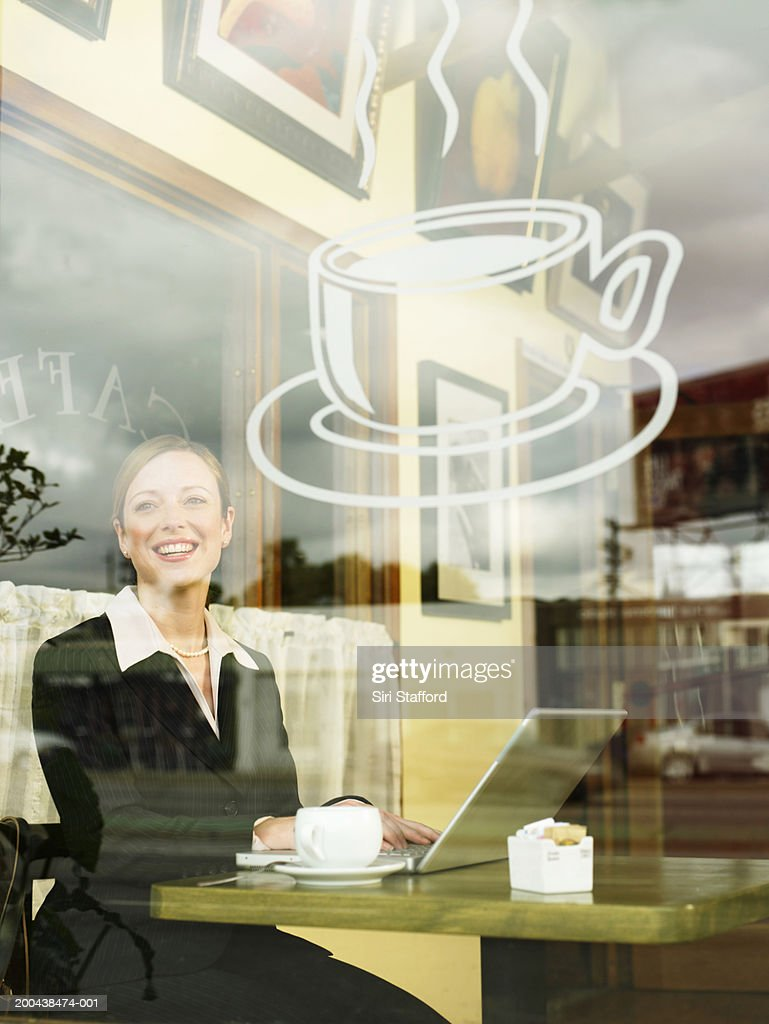Businesswoman sitting in  coffee shop with laptop computer : Stock Photo