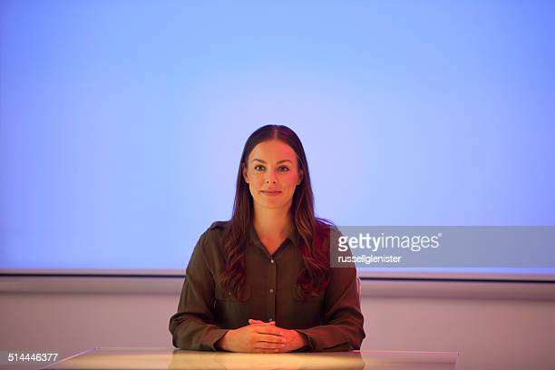 Businesswoman sitting in front of blank screen in office conference room