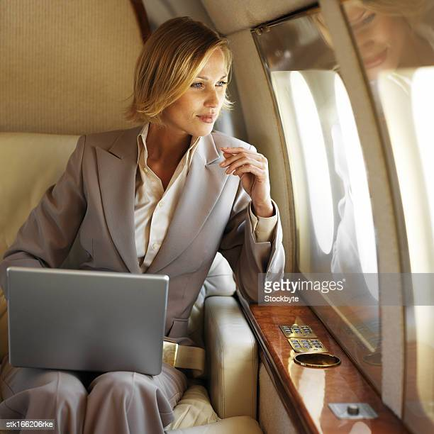 businesswoman sitting in front of laptop looking out the window