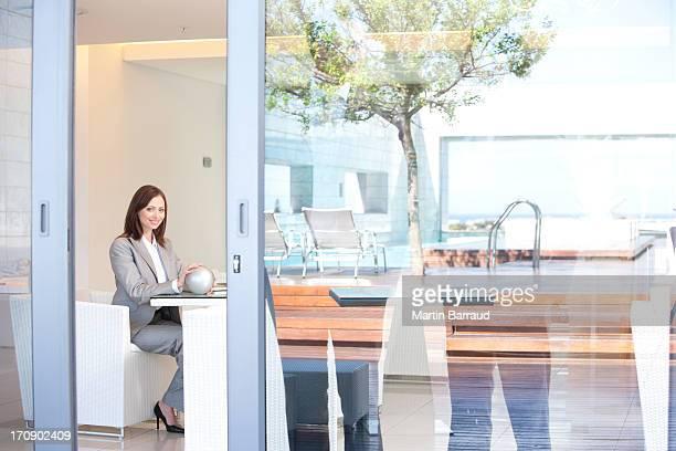 Mulher de Negócios sentado no lobby do hotel segurando Esfera