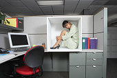 Businesswoman sitting in office cubicle