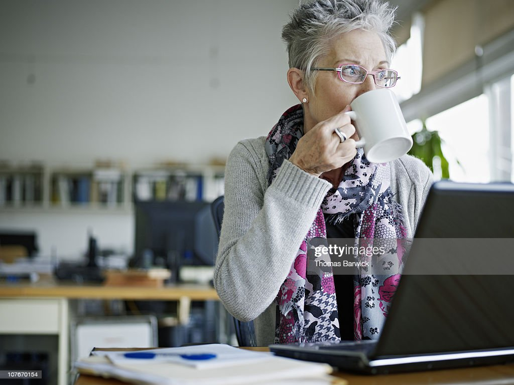 Businesswoman sitting in office drinking coffee : Photo