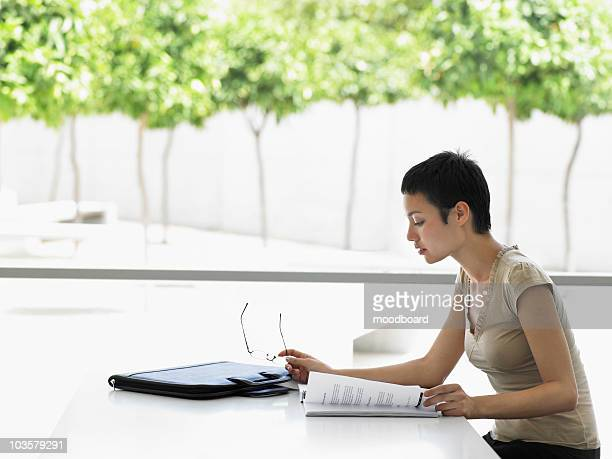 Businesswoman sitting in office looking at files