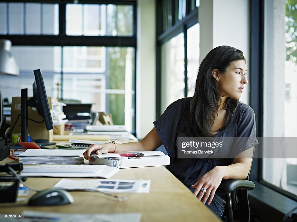 Businesswoman sitting in office looking out : Stock Photo