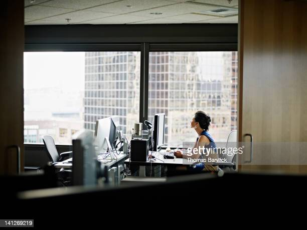 Businesswoman sitting in office looking out window