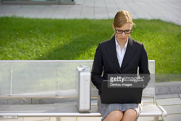 A businesswoman sitting on a bench using a laptop.