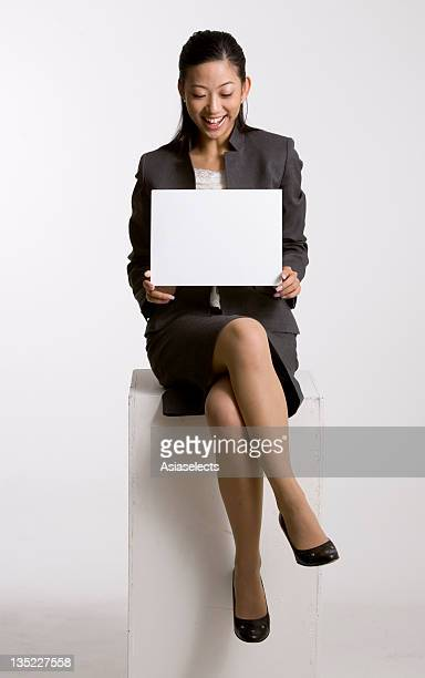 Businesswoman sitting on a stool and looking at a placard