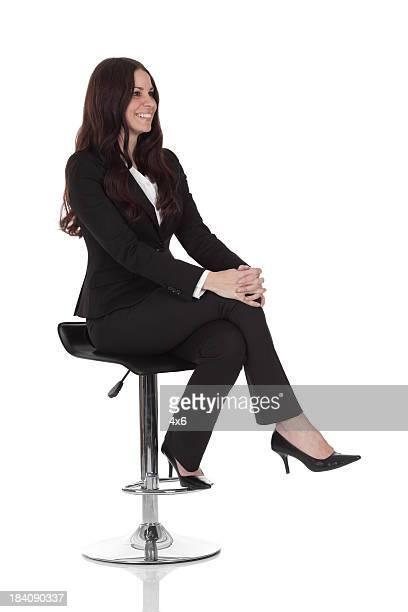 Geschäftsfrau sitzt auf einem Barhocker