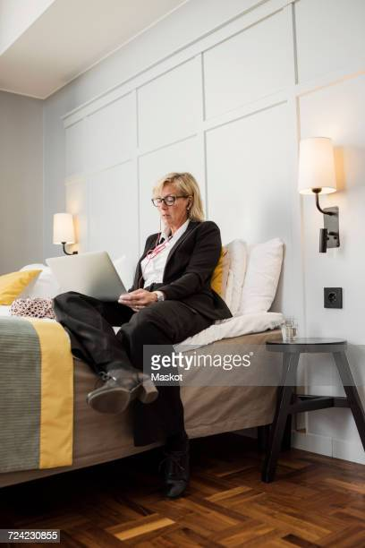 Businesswoman sitting on bed using laptop against wall in hotel room