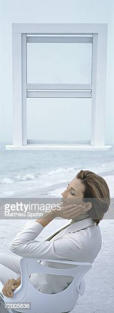 Businesswoman sitting on chair on beach with eyes closed, open window in background