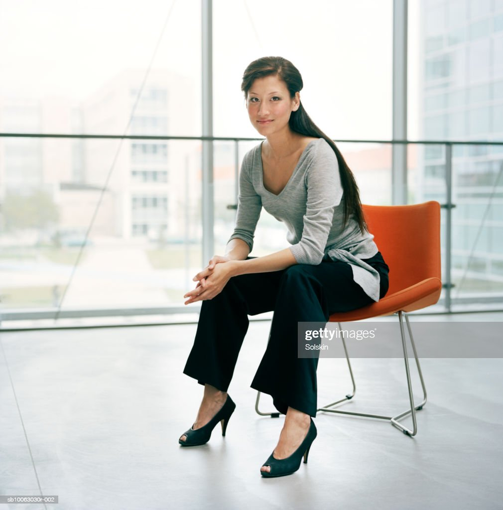 Businesswoman sitting on chair, smiling, portrait : Stock Photo