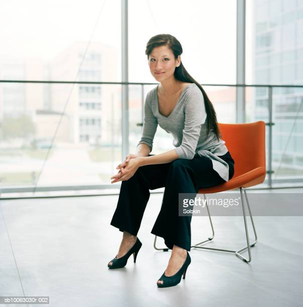 Businesswoman sitting on chair, smiling, portrait