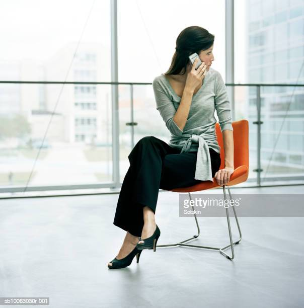 Businesswoman sitting on chair using mobile phone