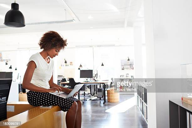 Businesswoman sitting on counter typing on laptop