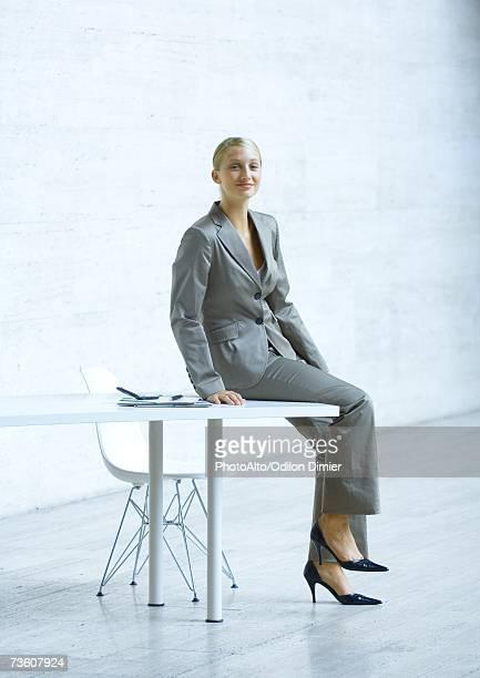 Businesswoman sitting on edge of table, full length portrait