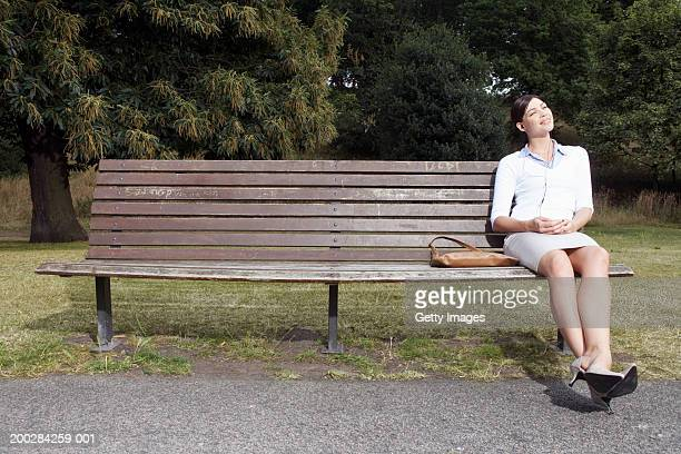 Businesswoman sitting on park bench, listening to mp3 player, smiling
