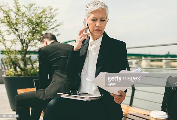 Businesswoman Sitting On The Bench And Talking On Her Phone.