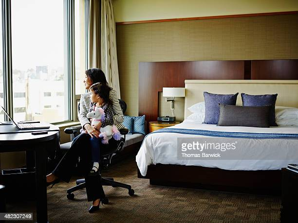 Businesswoman sitting with daughter in hotel room