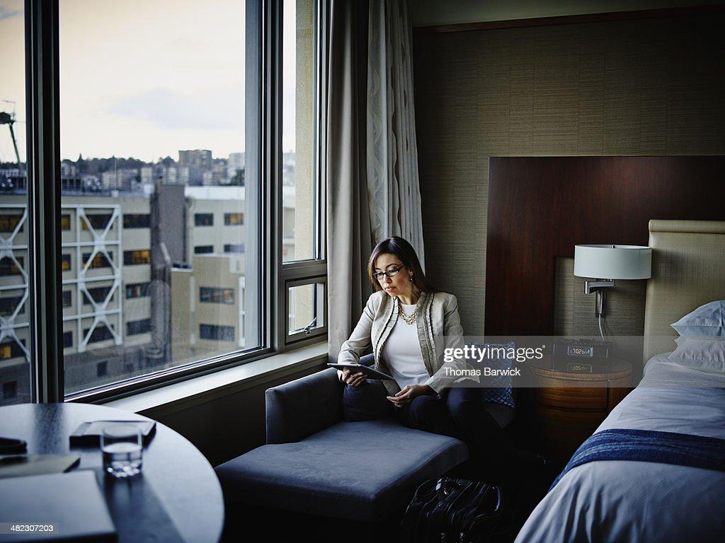 Businesswoman sitting working on digital tablet : Stock Photo