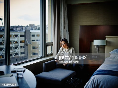 Businesswoman sitting working on digital tablet : Stock Photo