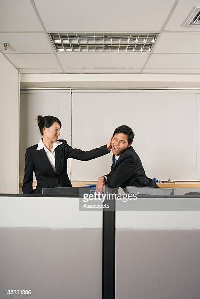 Businesswoman slapping a businesswoman from office cubicle