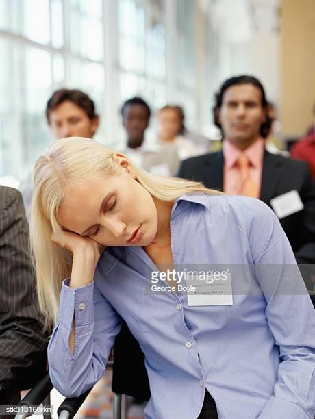 businesswoman sleeping at a seminar