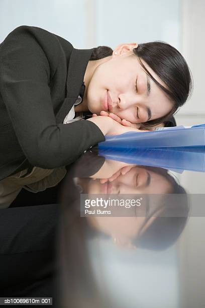 Businesswoman sleeping at desk, close-up, side view