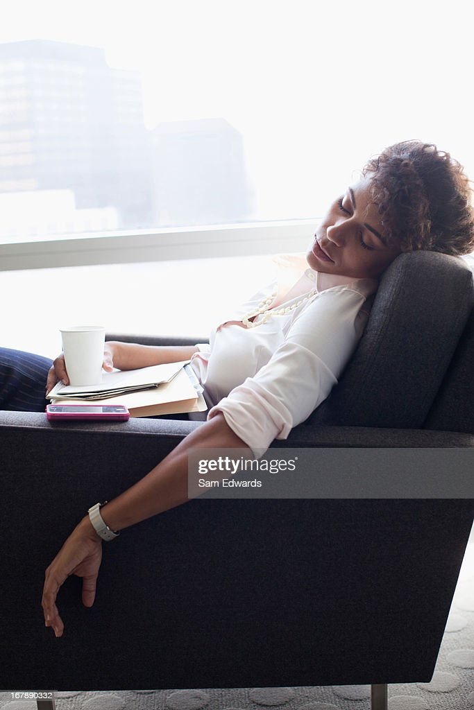 Businesswoman sleeping in office chair : Stock Photo