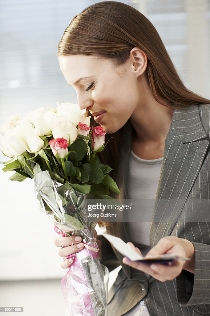Businesswoman smelling bouquet of flowers and holding card : Stock Photo
