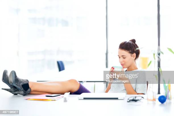 Businesswoman Smelling Coffee With Feet Up At Office Desk
