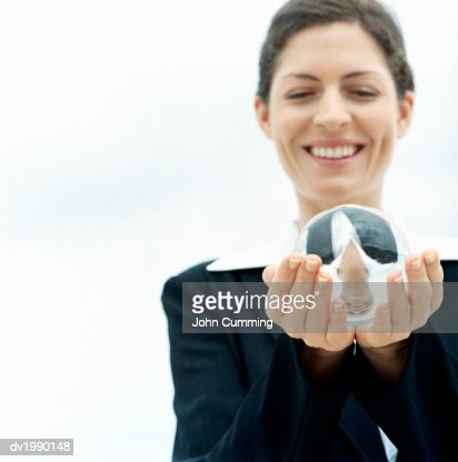 Businesswoman Smiles at a Crystal Ball in Her Hands : Stock Photo