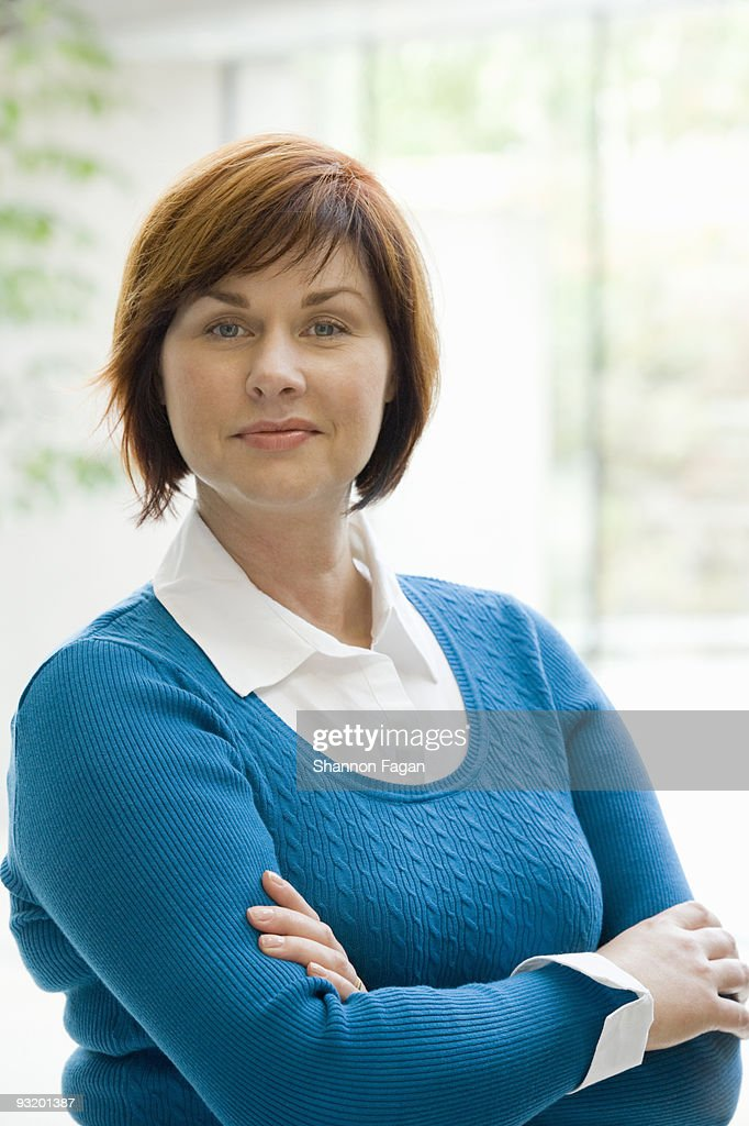 Businesswoman smiling and crossing arms : Stock Photo