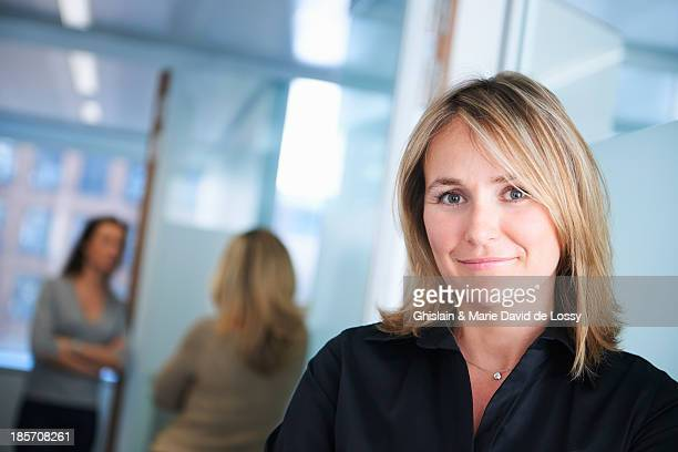 Businesswoman smiling at camera, co-workers behind