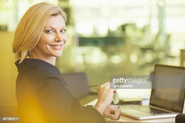 Geschäftsfrau Lächeln am Schreibtisch in Büro