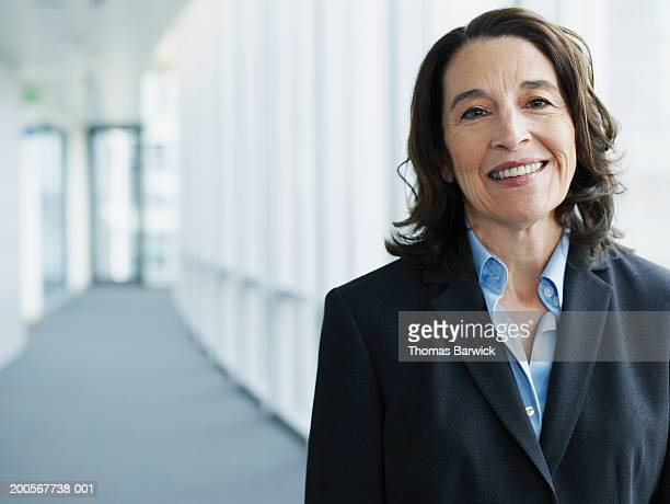 Businesswoman smiling in hallway, smiling, portrait