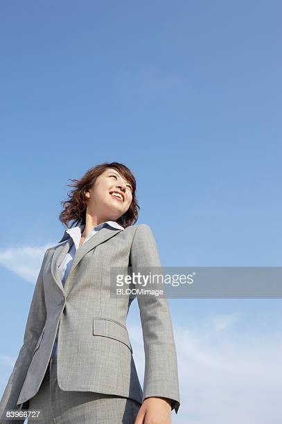 Businesswoman smiling, looking away, against blue sky