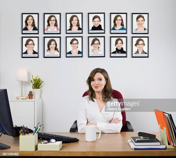 Businesswoman smiling under award pictures in office