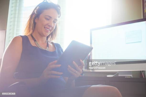 Businesswoman smiling whilst using digital tablet