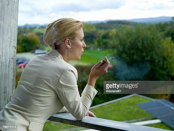 Businesswoman smoking on balcony