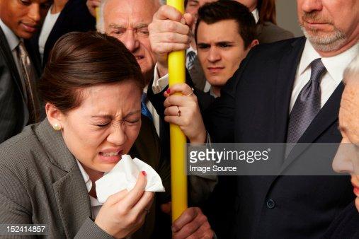 Businesswoman sneezing on subway train