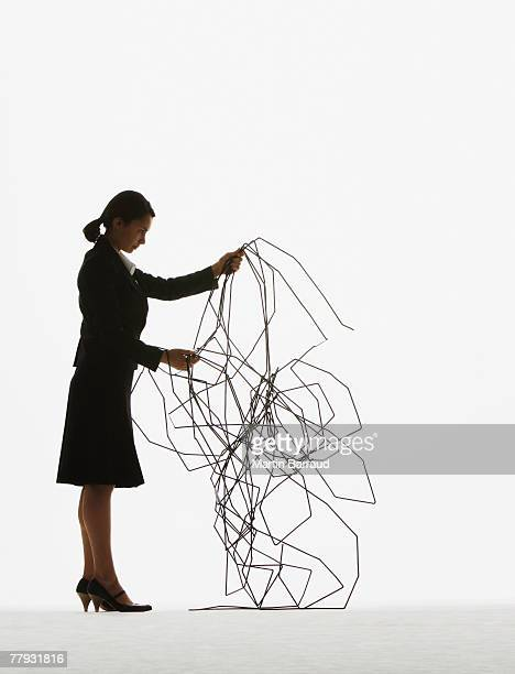 Businesswoman sorting through a pile of cable