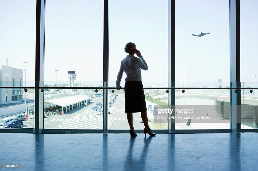 Businesswoman standing at airport window