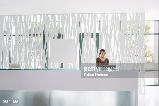 Businesswoman standing at office reception desk