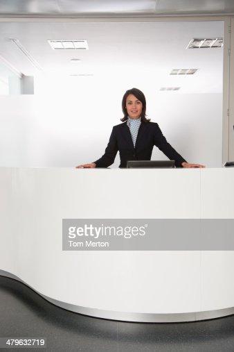 Businesswoman standing at reception desk