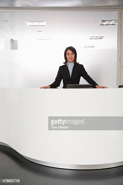 Businesswoman standing at reception desk