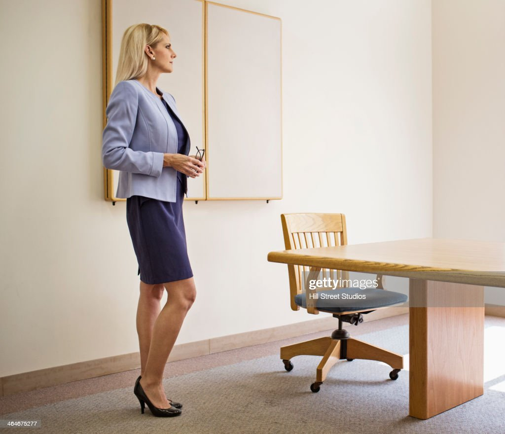 Businesswoman standing at table in conference room : Stock Photo