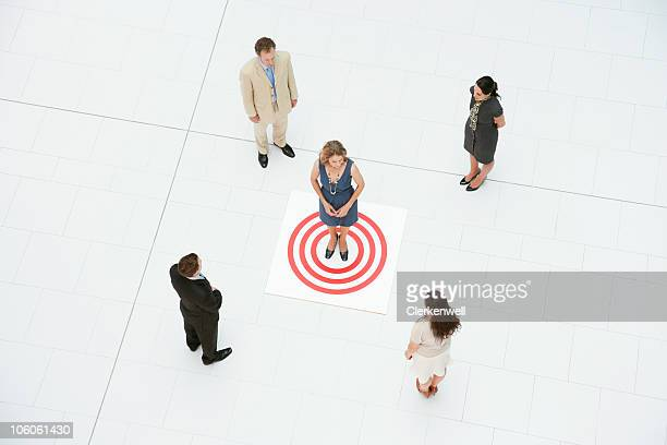 Businesswoman standing at target with her colleagues around