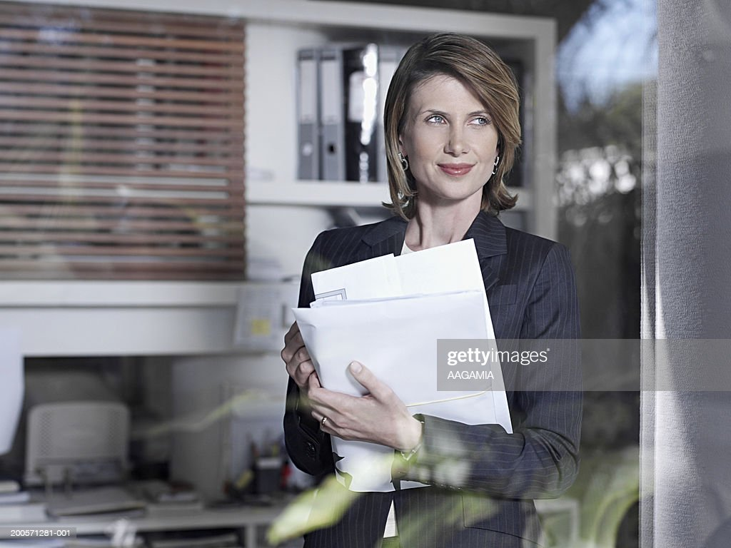 Businesswoman standing behind window with holding documents in office : Stock Photo