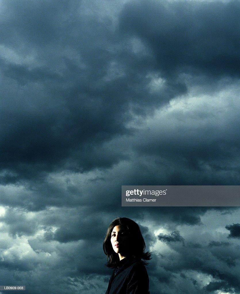 Businesswoman standing beneath stormy sky, portrait : Stock Photo
